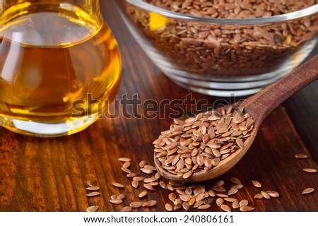 Brown flax seeds on spoon and flaxseed oil in glass jug on wooden table. Flax oil is rich in omega-3 fatty acid. - stock photo
