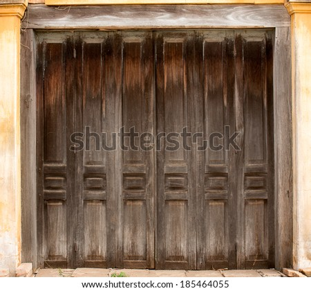 Brown folding doors of abandoned building - stock photo
