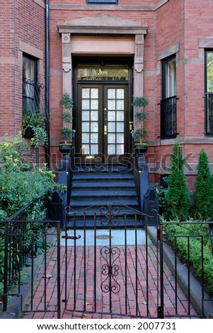 Brown french double doors sitting stately atop of black painted stairs behind an iron gate - stock photo