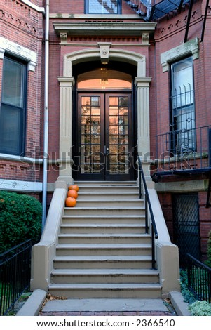 Brown french double doors sitting stately atop of cement stairs adorned with pumpkins - stock photo