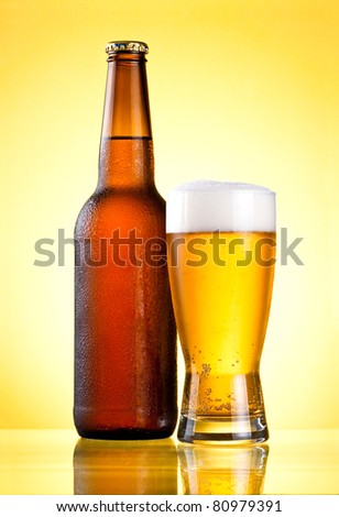 Brown full bottle covered with condensate and glass fresh cold beer on yellow background