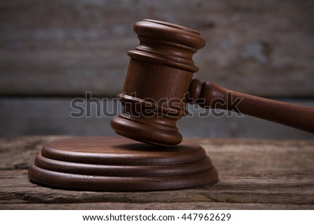 Brown gavel with stand. Gavel on old wooden surface. Freedom is the most precious. Avoid trial at all costs.