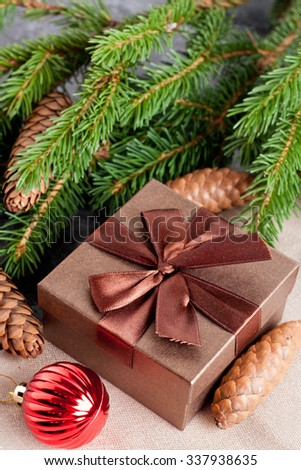 brown gift box, Christmas ball and Green fir branches on black background, closeup, top view, vertical - stock photo