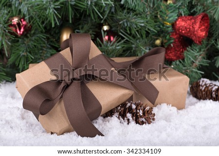 Brown gift box on snow with holiday background - stock photo