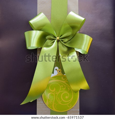 Brown gift box with green ribbon bow - stock photo