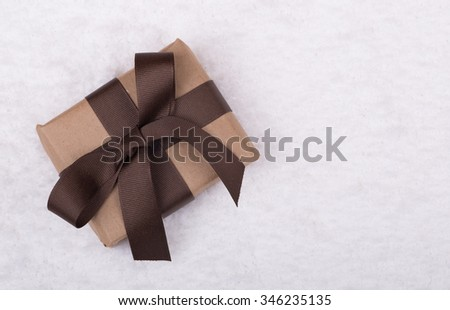 Brown gift box with ribbon and bow on snow