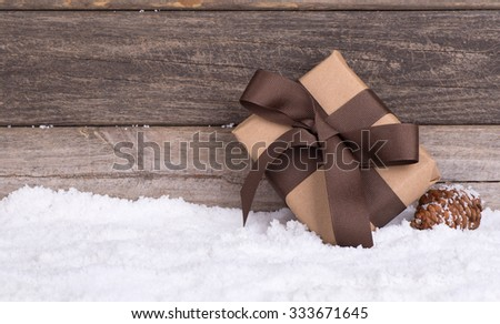 Brown gift on snow with wood background - stock photo