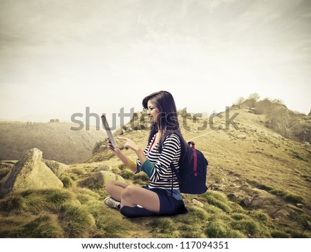 Brown girl using a tablet pc in a mountain landscape