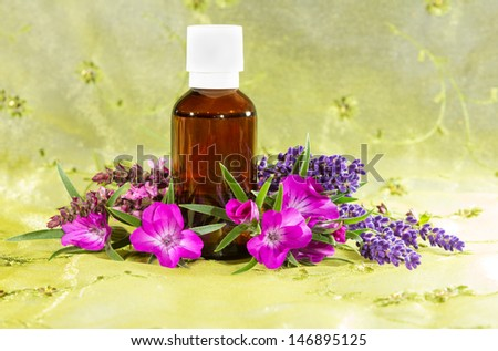 Brown glass bottle of essential oil plant extracts with fresh flowers of lavender and sidalcea, or prairie mallow, for use in aromatherapy and as a spa massage oil - stock photo