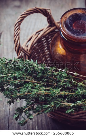 Brown glass pharmacy bottle and thyme herb in a wicker basket vintage style on old wooden board. - stock photo