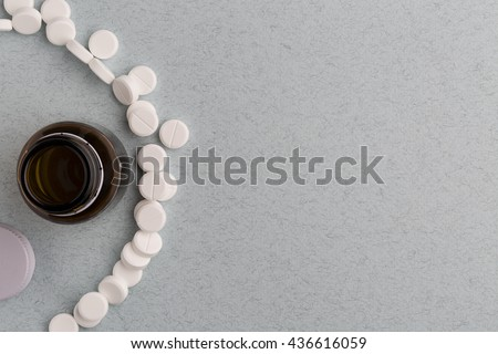 Brown glass pill bottle and white pills - stock photo