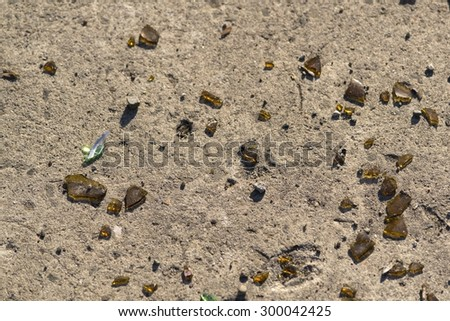 Brown glass shards on cement floor