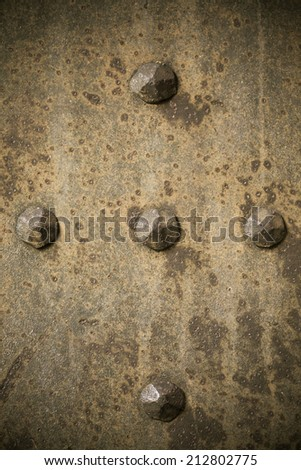 Brown grunge metal plate or armour texture with rivets as background - stock photo