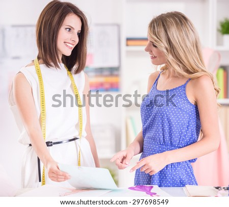 Brown hair and blond hair women looking to each other and discussing work questions at studio. - stock photo