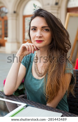 Brown hair girl sitting behind table in caf���© restaurant and smiling