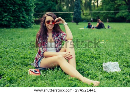 Brown hair girl spending free time, sitting on the grass in the park, relaxing - stock photo