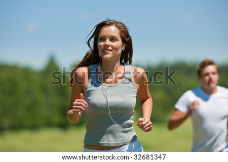 Brown hair woman with headphones jogging, man in background, shallow DOF - stock photo