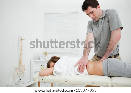Brown-haired doctor massaging the back of a woman in a room - stock photo