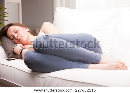 brown haired girl sleeping on her couch in a white living room - stock photo