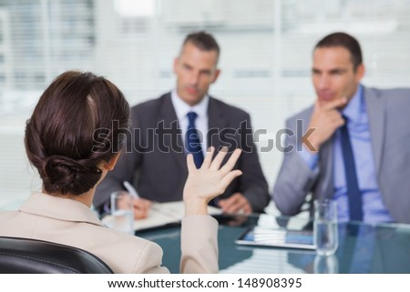Brown haired woman talking to her interviewers  in bright office - stock photo