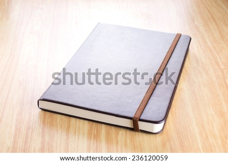 Brown Hard cover notebook with elastic strap on wooden table in perspective view,Template for adding your title - stock photo
