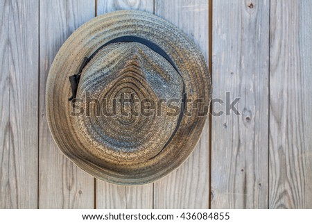 brown hat headband hanging on weathered wooden wall of old barn - stock photo