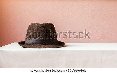brown hat on table with pink background - stock photo