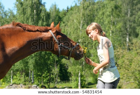 Brown horse with smiling girl offering flowers - stock photo