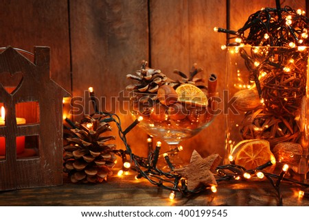 Brown house with candle and electric garland on wooden background - stock photo