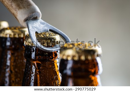 Brown ice cold beer bottles with water drops and old opener - stock photo