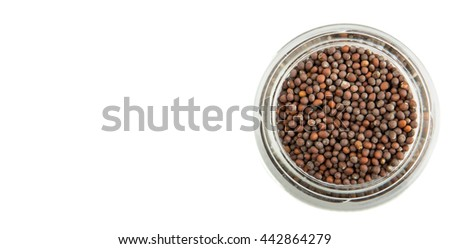 Brown Indian mustard seed in mason jar over white background