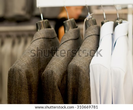 Brown jackets on hangers in boutique. - stock photo