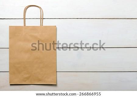 brown kraft bag on wood white desk - stock photo