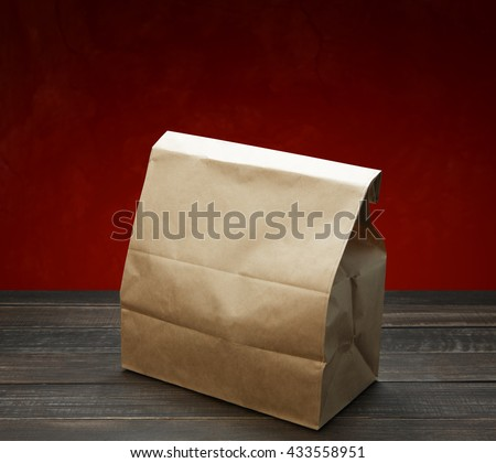 Brown kraft paper bag for lunch or food on wooden table at red background. Wrapping paper bag with copy space. Food bag for lunch or food take away delivery. Ecological natural bag. - stock photo