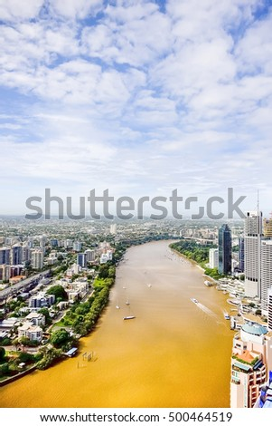 Brown lake with boats and buildings near city, town has huge apartments and green forests, river has some small white boats with people, weather is good with blue sky and white clouds.