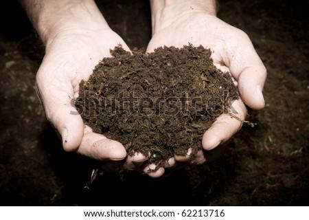 Brown  Land and humman hand (on hand) - stock photo
