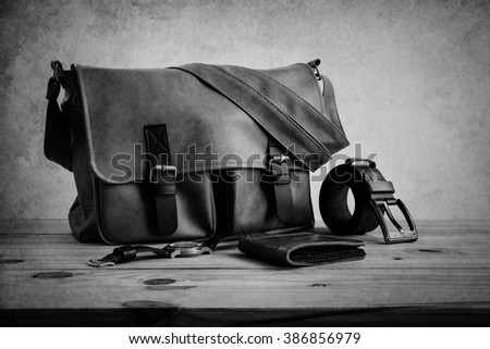 Brown leather bags with men's accessories on wooden table over wall background, black and white - stock photo