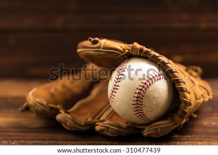 Brown leather baseball glove on a wooden bench - stock photo