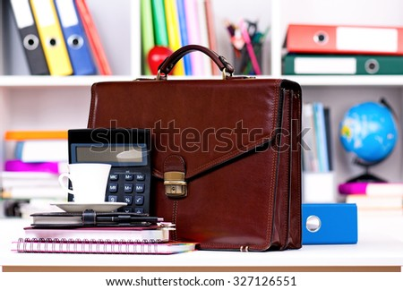 Brown leather briefcase on table at office - stock photo