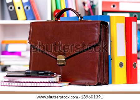 Brown leather briefcase with office accessories, isolated on white background - stock photo