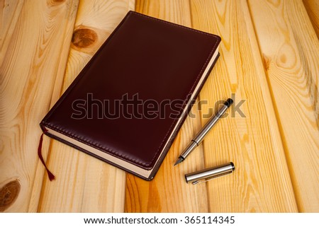 Brown leather daily planner with pen on wooden table - stock photo