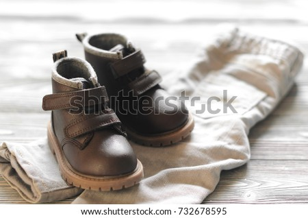brown leather kids shoes and denim pants on wood backdrop