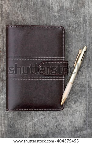 brown leather notebook and ballpoint pen on grunge wooden background - stock photo