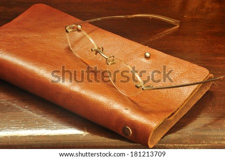 brown leather notebook and glasses on wooden background - stock photo