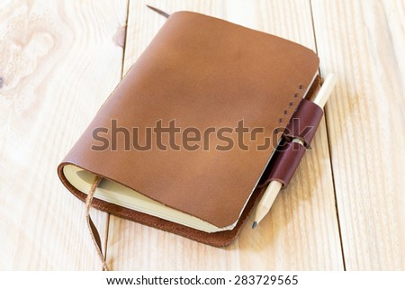 Brown Leather notebooks on wooden table - stock photo