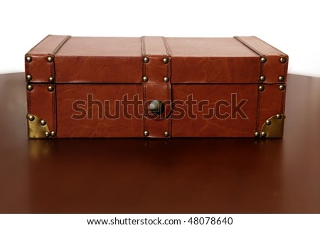 Brown leather suitcase over warm wooden table
