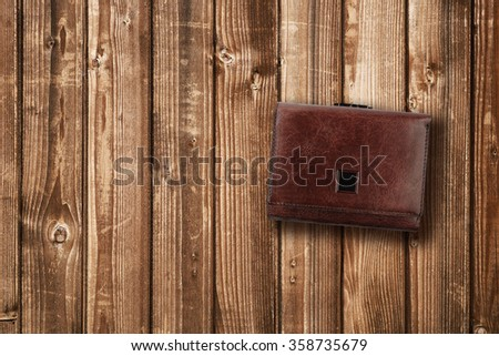 Brown leather wallet on wooden background - stock photo