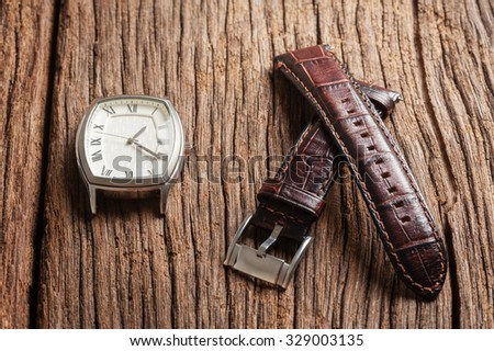 brown leather watch band on wooden table - stock photo