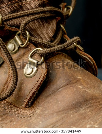 Brown leather work boots on black background