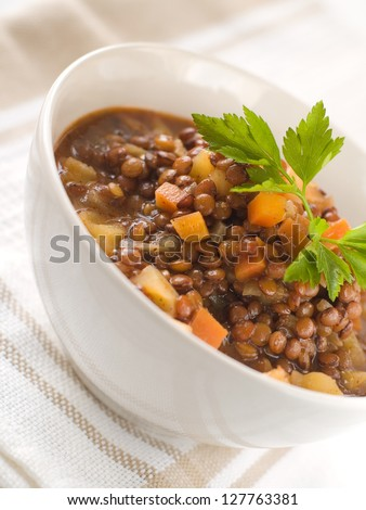 Brown lentil stew in bowl with vegetable, selective focus